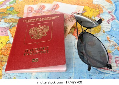 Sunglasses and Russian international passport with money on the world map