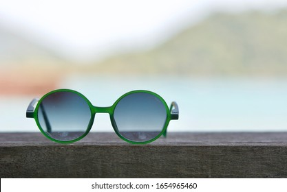 Sunglasses with sea and mountain view background, Fashion sunglasses on wood table with blue cloudy sky, Summer holiday. Beautiful Relaxing background. Copy space.