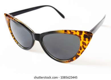 Sunglasses in the shape of cat's eye, women's fashion, leopard frame in black and brown, dark glasses, white background.