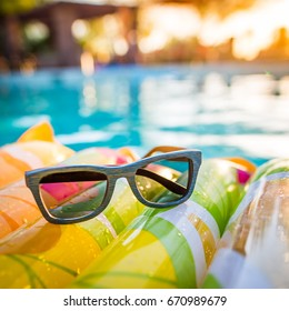 Sunglasses sitting relaxed on raft poolside at sunset.