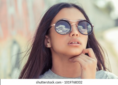 Sunglasses sky view reflection. Closeup portrait confident successful beautiful attractive brunette young woman fashion girl model posing, with goggles sun glasses hand on head on graffiti wall