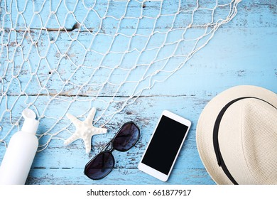 Sunglasses with smartphone, hat and starfish on wooden table