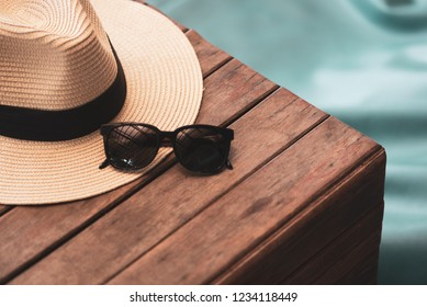 Sunglasses and straw hat on the wooden floor at the beach, summer concept.