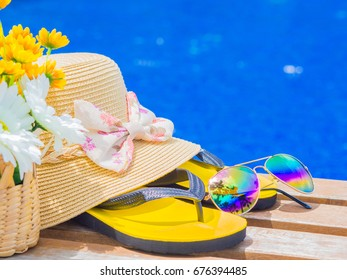 Sunglasses with summer hat, flip flops, shampoo, sunscreen lotion  and flowers by the swimming pool. Vacation and relaxation, summer travel concept.