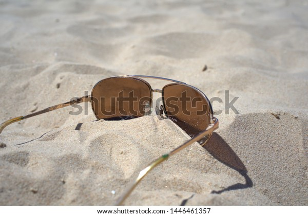 Sunglasses sunk in the sand on the hot beach
