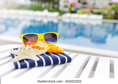 Sunglasses and the things on a poolside lounger.