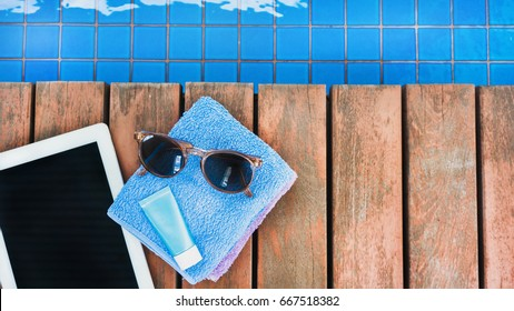sunglasses, towel, tablet and sunscreen at the side of swimming pool. Vacation, beach, summer travel concept