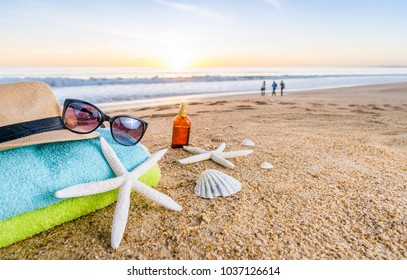 Sunglasses, towels, hat, sun block, shells and starfish on sandy beach
