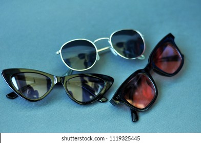 Sunglasses of unusual trend models on a neutral background
