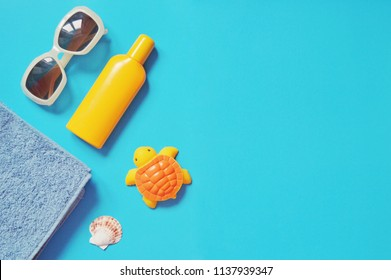 Sunglasses, yellow sunscreen bottle, towel and turtle toy. Flat lay travel photo. Summer holiday, beach relaxation