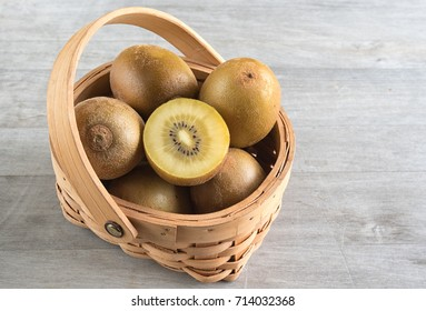 Sungold Kiwi or kiwifruit in a basket over a wooden background.