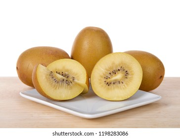 Sungold kiwi sliced in half with whole fruit behind on white plate on wood table. Unlike Green Kiwifruit, new SunGold Kiwifruit have a smooth skin and is less acidic than typical Kiwi fruit.