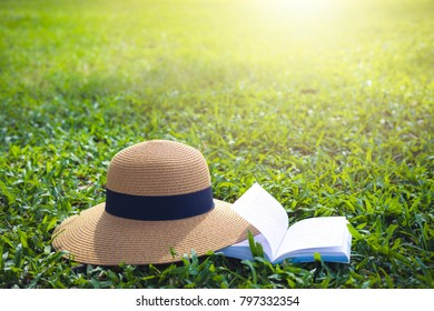 Sunhat and book lying on a lush green grass under the hot rays of the sun
