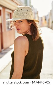 Sunhat girl turning to smile at camera from street, portrait