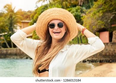 Sunhat and shades girl on beach, portrait