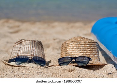 Sunhats and sunglasses on the sand near the blue inflatable matress against the sea.