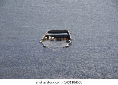 Sunken boat submerged under sea water.  The boat is surrounded by grey tranquil water.