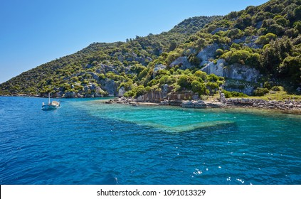 Sunken city of Kekova in bay of Uchagiz view from sea in Antalya province of Turkey with turqouise sea rocks and green bushes with remains of ancient city visible under water.