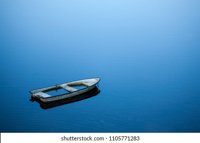 sunken rowboat in a quiet blue lake