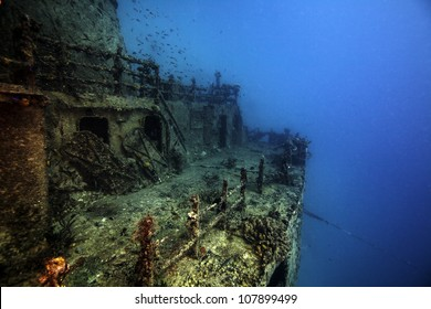 The sunken shipwreck Eagle in the Florida Keys. A ship laying in the sand on it's side with the wreck broken in half. Blue water surrounding coral covered boat. with a lot of fish and animals.