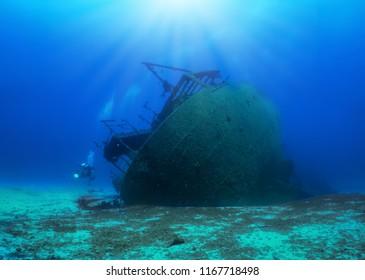 A sunken shipwreck in the mediterranean sea with a scuba diver, Greece