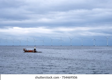 Sunken shipwreck with only the top sticking out of the water, with a row of windmills in the background, near Amager Strandpark in Denmark