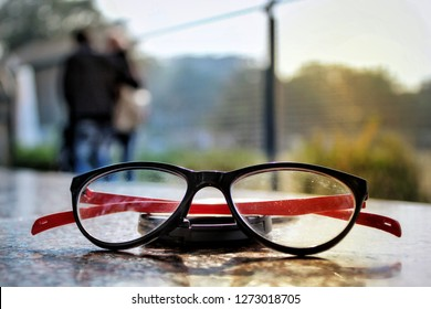 a sunkissed sunglass with red and black rim couples in background