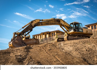 SUNLAND, CALIFORNIA, UNITED STATES, December 27, 2015: A backhoe rests on a construction site, framing a newly-completed house in the background.