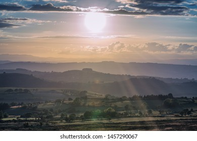Sunlight beams over scenic countryside hills in Shropshire, United Kingdom