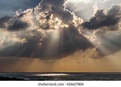 Sunlight beams through a cloudy sunset on the beach