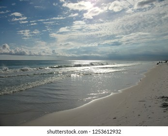 Sunlight breaks through the cumulus clouds drifting overhead as gentle waves lap against the beach in Destin, Florida.