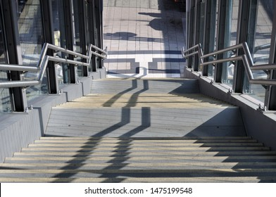 sunlight casting shadows on concrete steps leading from pedestrian bridge over railway station to platform