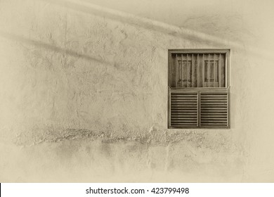 Sunlight casts shadows and brings out relief across an adobe plaster wall with a wooden shuttered window in the exterior wall of a traditional Arabian house.