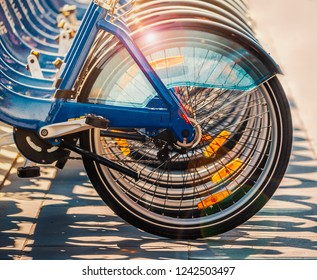 sunlight catching the rims of a row blue city bikes causing an attractive lens flare and shadows. Each bicycle has orange reflectors on the spokes and transparent  plastic mud guards