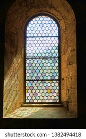 Sunlight colored by unique stained glass leaded window in a monastery floods in to highlight the thick ancient walls of the  interior of the building.