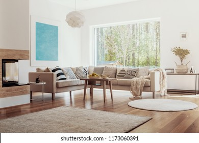 Sunlight coming through a large window into a white and beige living room interior with fruit bowls on a wooden table