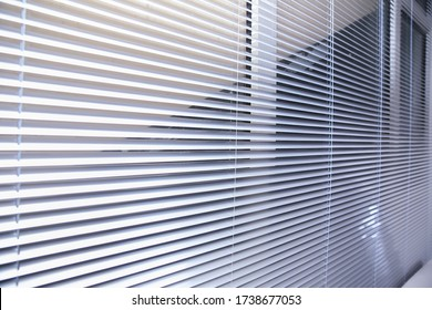 Sunlight coming through venetian blinds by the window . Office blinds. Modern wooden jalousie. Office meeting room lighting range control. venetian blinds by the window