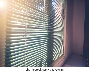 Sunlight coming through venetian blinds,Windows blind by the window.soft focus and soft light for blurred background.Soft vintage style.