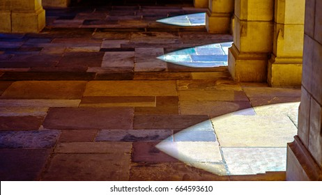 Sunlight falls onto slate tiles through stone archways at the University of Melbourne in Australia