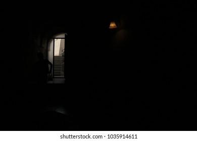Sunlight get inside from a door. Opening door in a dark room with shining light