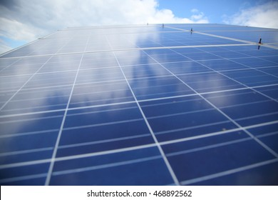 Sunlight gleams off solar panels. Solar panels used to generate electricity from sunlight against clouds and sky. In selected focus. Close-up. Shallow depth of field.