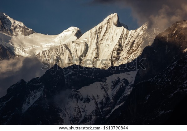 Sunlight hits a peak of the Annapurna range on the Annapurna Base camp trail in the Nepal Himalayas.