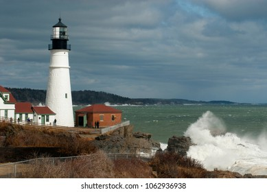 Sunlight illuminates Portland Head lighthouse in Maine through storm clouds as huge waves break over rocks nearby.