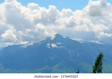 Sunlight illuminates a snowy mountain peak, although storm clouds are gathering. Forest covers the lower slopes of the mountain.