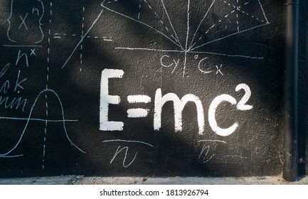 Sunlight laterally illuminates a white graffiti on the wall on a black background The Mathematical Formula on the Transformation of Energy into Matter