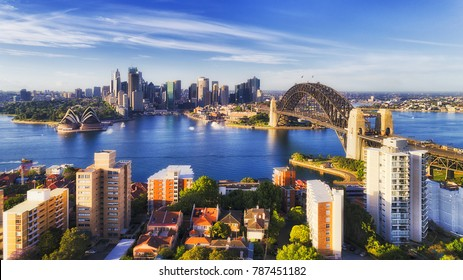 Sunlight on a bright sunny day on major Sydney city and Australia landmark around sydney harbour from Kirribilli suburb on north shore towards CBD high-rise towers across blue water.