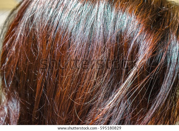 sunlight on ginger brown burgundy red hair with long waves and gradient effect. Straight hair fragment as a texture. long hair as natural background
