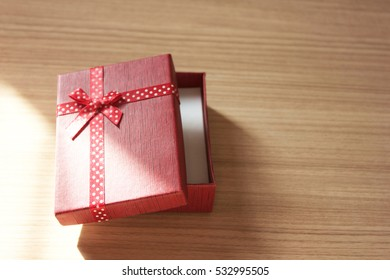 sunlight on red present box with wood background