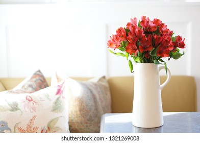 Sunlight on table with white pitcher of red alstroemeria flowers next to floral covered pillow