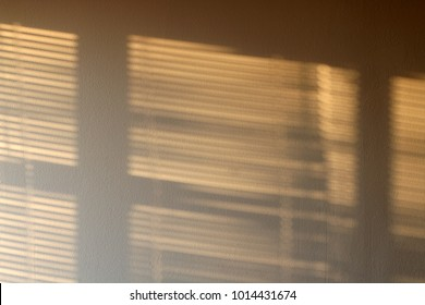 Sunlight on the wall, peeking through the blinders. Abstract background, copy space.